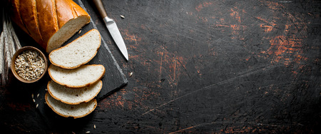 Pieces of bread with a knife, grain and spikelets. On dark rustic background