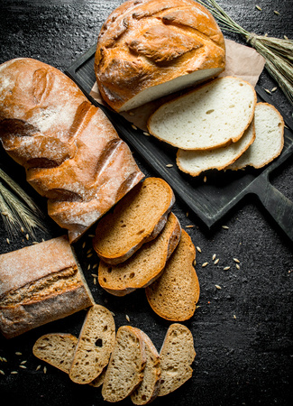 Pieces of different types of bread. On black rustic background Banque d'images