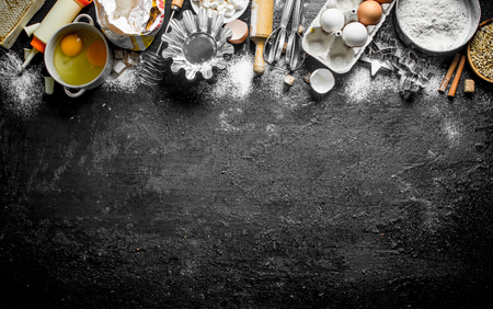 Flour with different baking forms of the dough. On black rustic background