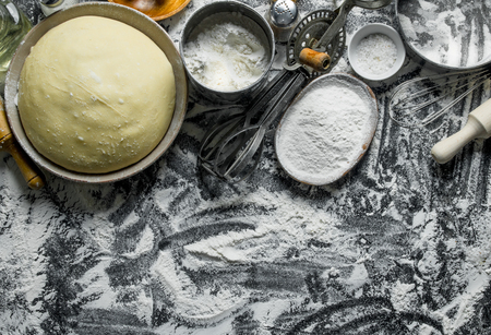Dough and flour in bowls. On rustic background