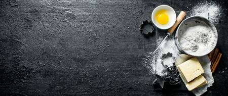 Baking background. Flour with egg, butter and various forms for baking. On black rustic background
