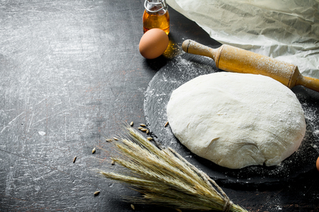 Fresh dough with spikelets and a rolling pin. On dark rustic background