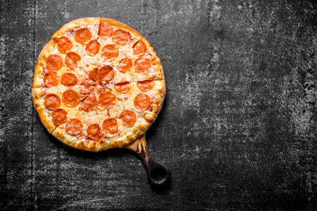 Fragrant pepperoni pizza on the cutting Board. On dark rustic background