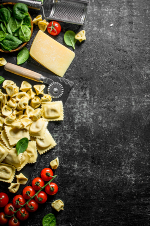 An assortment of different types of raw pasta with cheese, tomatoes and herbs. On dark rustic background Stok Fotoğraf