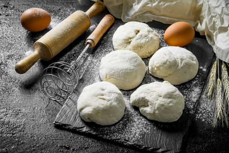 Round pieces of dough with eggs and rolling pin. On black rustic background