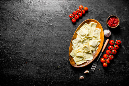 Ravioli with sauce, cherry tomatoes and garlic cloves. On black rustic background
