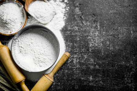 Flour in a sieve and bowl. On dark rustic background
