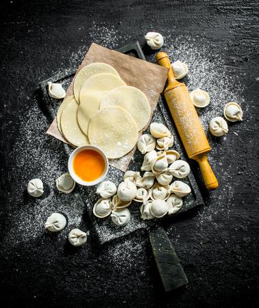 Raw dumpling with dumpling dough. On black rustic background