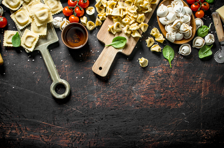 Different kinds of traditional Italian raw pasta. On dark rustic background