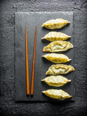 Chinese gedza dumplings on a black stone Board. On black rustic background