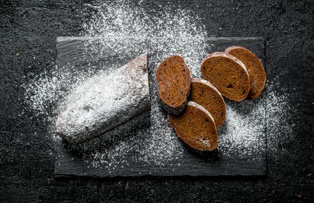 Sliced rye bread on a stone Board. On black rustic background Banco de Imagens