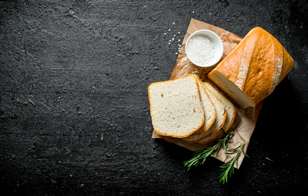 Pieces of fragrant bread with salt and rosemary. On black rustic background Stock fotó