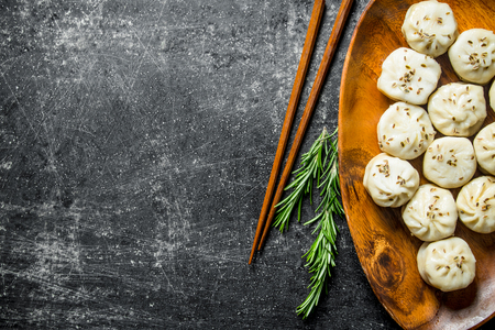 Dumplings manta on a plate with rosemary. On dark rustic background