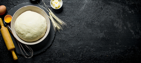 The dough in a bowl with a rolling pin, spikelets and eggs. On black rustic background