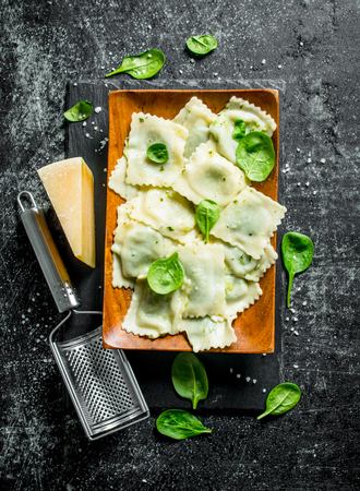 Ravioli with cheese and herbs. On dark rustic background