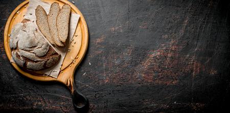 Rye bread on a round cutting Board. On dark rustic background