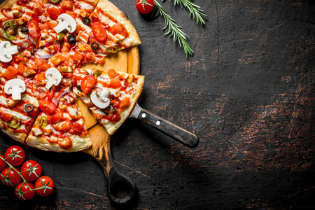 Sliced fragrant Mexican pizza on a cutting Board. On dark rustic background