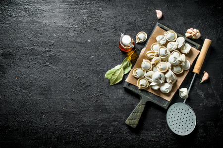 Freshly cooked raw dumpling on a cutting Board. On black rustic background