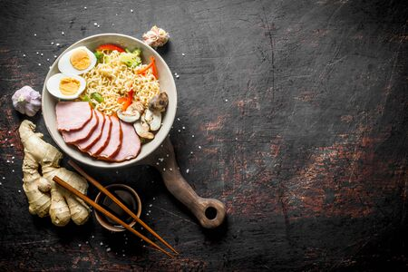 Instant noodles in bowl with ham, vegetables and egg on cutting Board. On dark rustic background