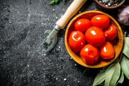 Homemade pickled tomatoes. On dark rustic background
