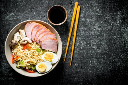 Instant noodles with vegetables, egg, ham, soy sauce and chopsticks. On dark rustic background Stock Photo