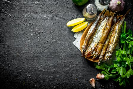 Smoked fish with lime slices, herbs and spices. On black rustic background