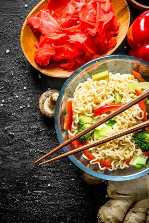 Readymade instant noodles with broccoli, pepper and ginger. On black rustic background
