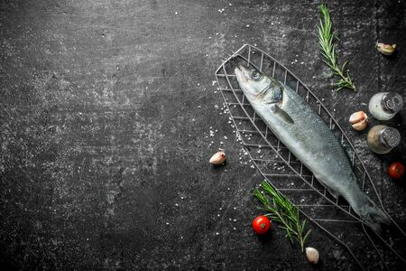 Raw fish on a grill rack with rosemary and spices. On dark rustic background