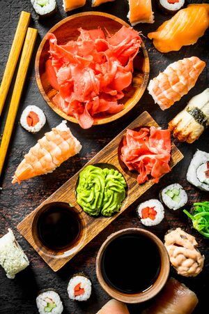 Assortment of different types of sushi, rolls and maki. On rustic background