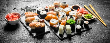 Different sushi rolls with chopsticks. On black rustic background