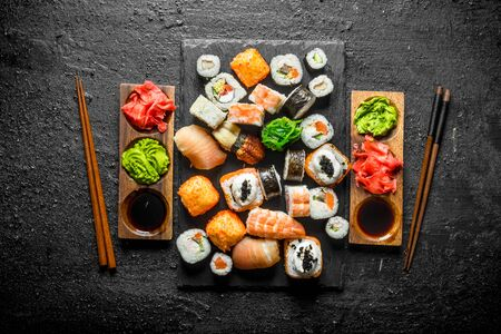 Set of Japanese sushi rolls for two with sauces and chopsticks. On black rustic background