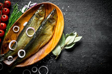 Smoked fish with tomatoes, dill and onion rings. On black rustic background Stock Photo