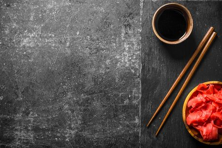 Soy sauce and marinated ginger on a stone Board with chopsticks. On dark rustic background