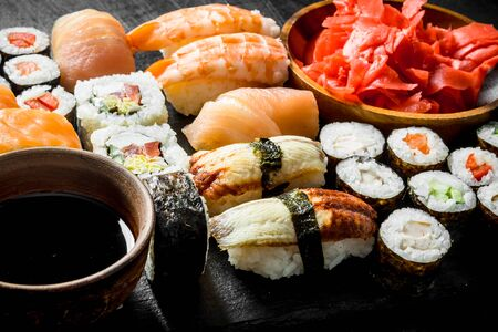 Various rolls, sushi and maki on a stone Board with soy sauce and ginger. On dark rustic background Stockfoto
