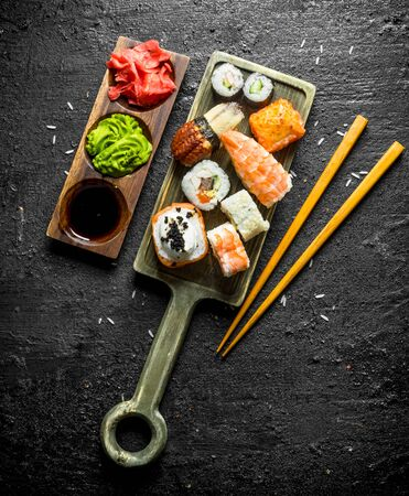 Sushi, rolls and maki on the cutting Board with chopsticks and sauces. On black rustic background Stockfoto