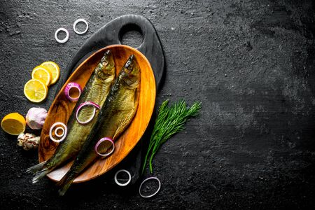 Smoked fish with dill, slices of lemon and onion. On black rustic background