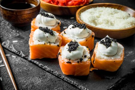 Delicious sushi rolls with salmon on a stone stand and soy sauce. On black rustic background