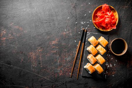 Freshly cooked Philadelphia sushi roll on a black stone stand. On dark rustic background Stockfoto