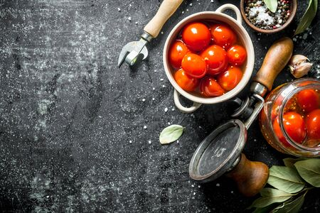 Homemade preserved tomatoes in a bowl and in a glass jar. On dark rustic background