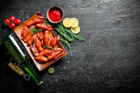 Fragrant boiled crayfish with beer, lemon slices and sauce. On black rustic background