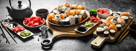 Assorted different types of Japanese sushi and rolls. On dark rustic background
