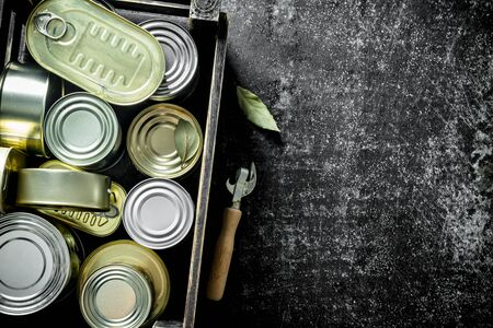 Closed metal cans with canned food in the box. On dark rustic background