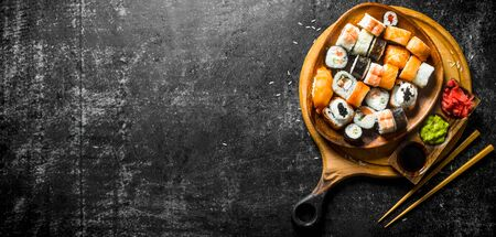 Fresh sushi rolls in a plate on a cutting Board with chopsticks and sauces. On dark rustic background Stockfoto