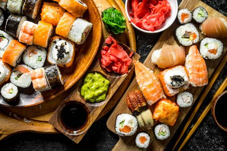A variety of sushi, maki and rolls with ginger and soy sauce. On rustic background
