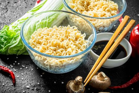 Instant noodles in bowls with mushrooms, Peking cabbage and soy sauce. On black rustic background Stock Photo