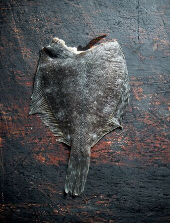 Raw fish flounder. On dark rustic background