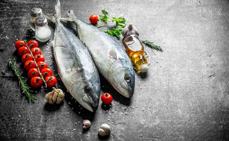 Raw fish with garlic, herbs and oil in a bottle. On dark rustic background