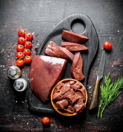 Raw liver with cherry tomatoes, spices and dill on a cutting Board. On dark rustic background