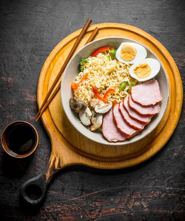 Instant noodles in bowl on cutting Board with becon, egg and mushrooms. On dark rustic background Stock Photo