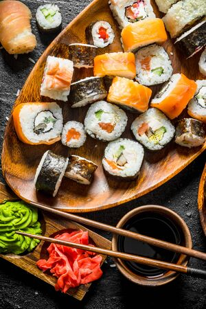 Pieces of delicious sushi, rolls and maki. On rustic background